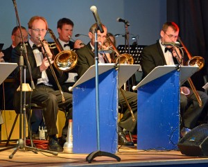 The band naturally has a strong brass section, partly obscured by the stage setting.