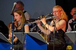 Some of the band members play different instruments, here swapping a sax for a flute.